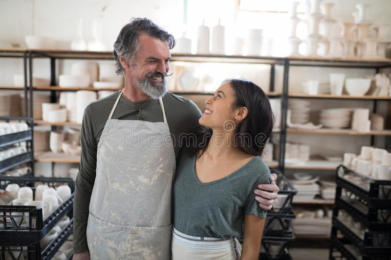 Smiling potter colleagues looking at each other. In the pottery workshop royalty free stock photos