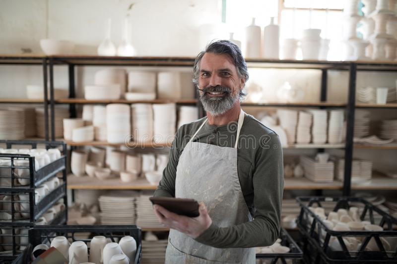 Smiling potter using tablet surrounded by work. In the pottery workshop stock photo