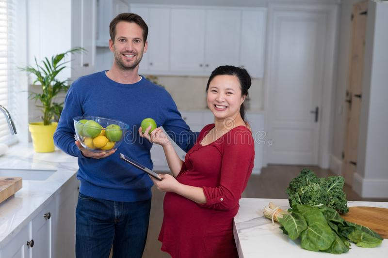 Pregnant couple holding sweet limes and digital tablet in the kitchen. Smiling pregnant couple holding sweet limes and digital tablet in the kitchen stock photos
