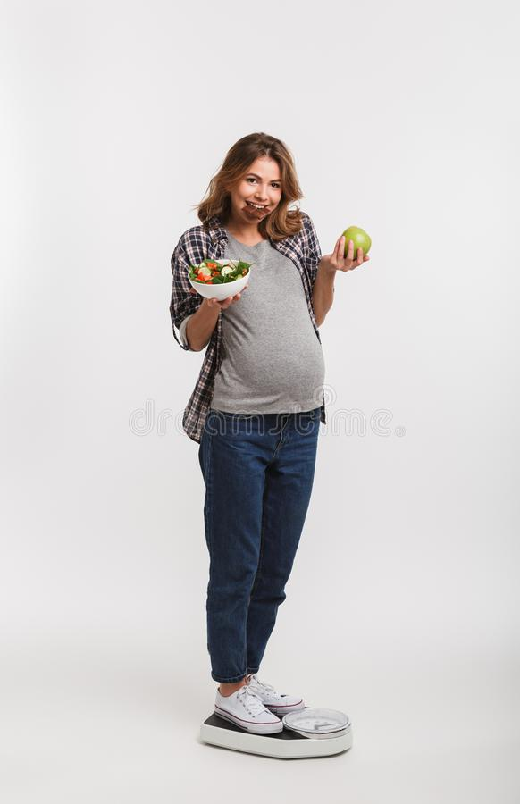 Smiling pregnant woman with chocolate apple and vegetable salad standing on scales. Isolated on white stock images