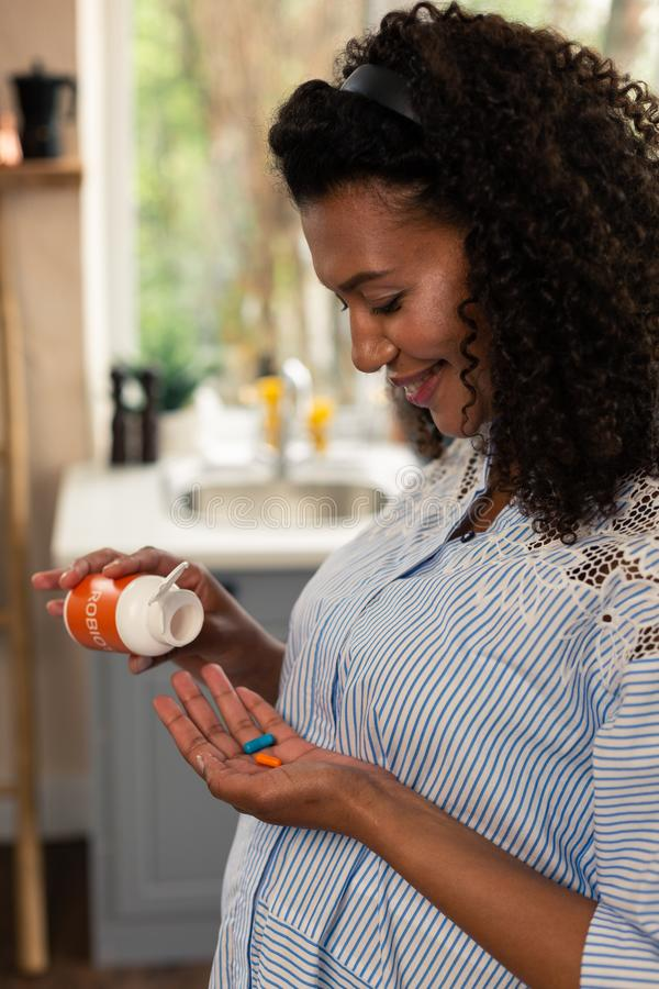 Smiling pregnant woman in process of taking vitamins. royalty free stock photos