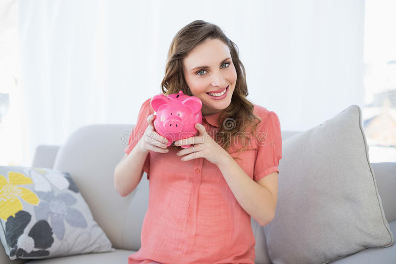 Smiling pregnant woman shaking pink piggy bank sitting on couch stock photo