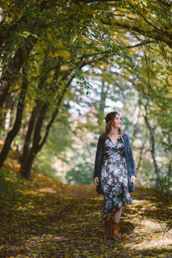 Smiling pregnant woman walking in autumn forest. royalty free stock image