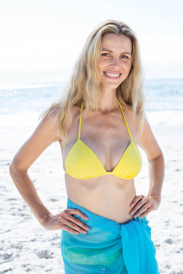 Free Smiling Pretty Blonde Standing By The Sea Hands On Hips Royalty Free Stock Images - 53055769