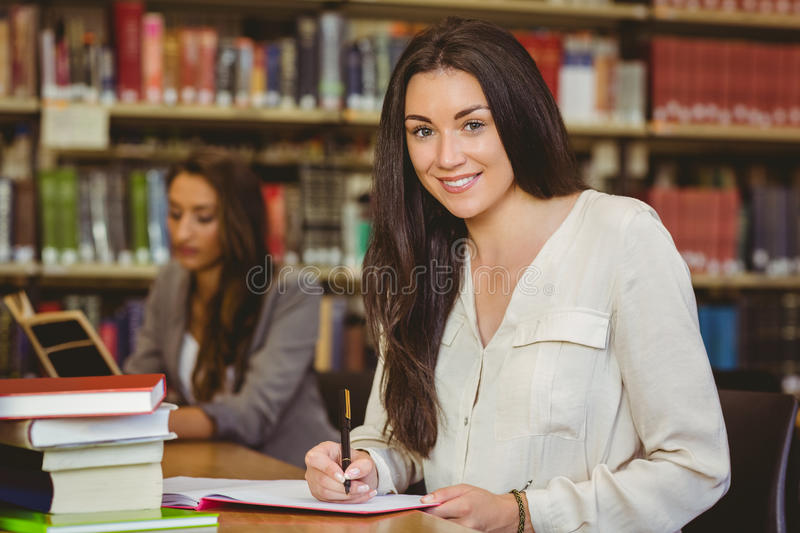 Smiling pretty brunette student writing in notepad royalty free stock photos