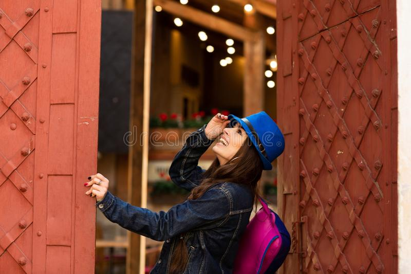Smiling pretty girl in blue hat near old building with antique red doors. Female model posing royalty free stock photo