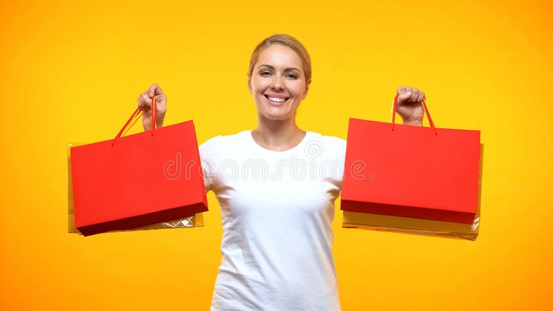 Smiling pretty lady showing shopping bags on orange background, holiday sale royalty free stock photography