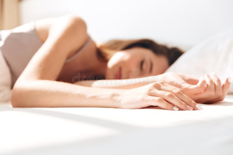 Smiling pretty lady sleep in bed indoors. Eyes closed. Picture of young smiling pretty lady sleep in bed indoors. Eyes closed royalty free stock images