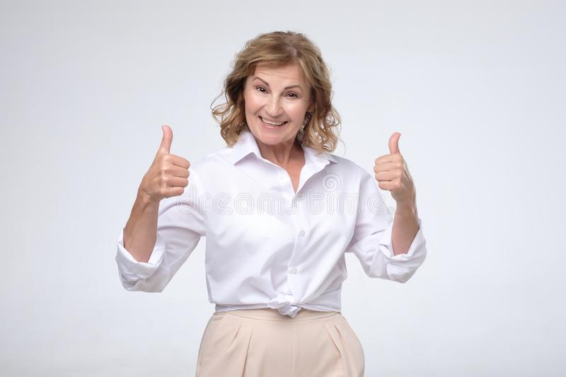 Smiling pretty mature woman showing thumbs up stock image