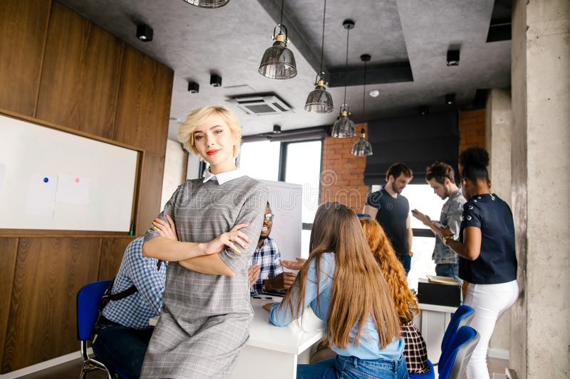 Smiling pretty model leaning on the office desk royalty free stock image