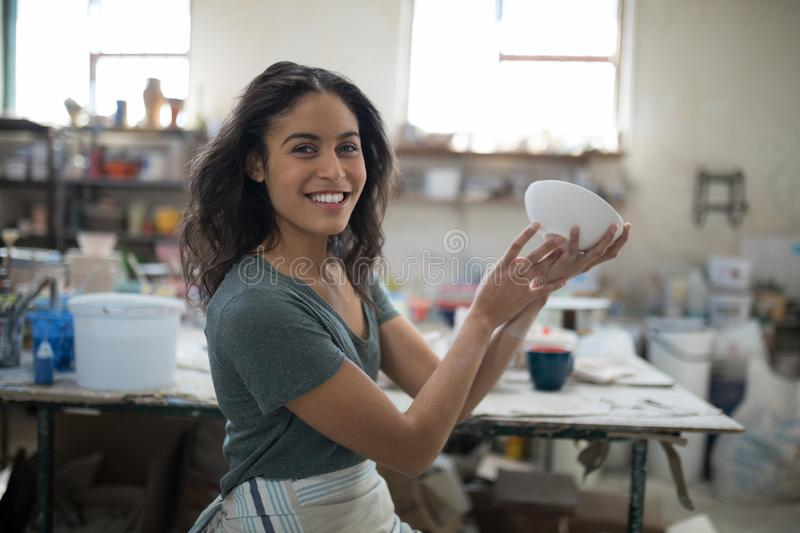 Smiling pretty potter examining her creation. In the pottery workshop stock images