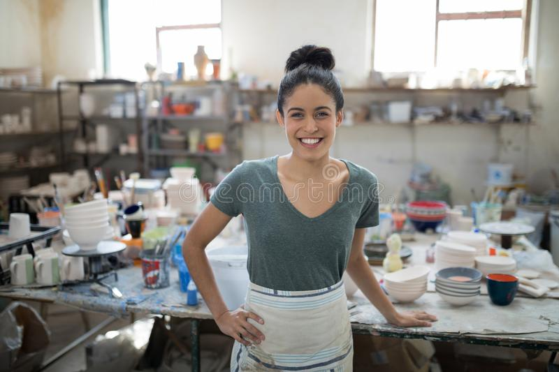 Smiling pretty potter looking at camera. In the pottery workshop royalty free stock images