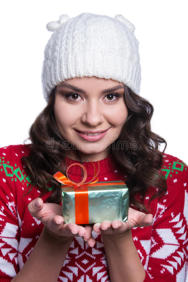 Smiling pretty young woman wearing colorful knitted sweater with christmas ornament and hat, holding christmas gift. royalty free stock photo