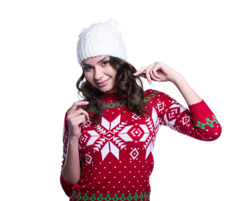 Smiling pretty young woman wearing colorful knitted sweater with christmas ornament and hat. Isolated on white background. stock photo