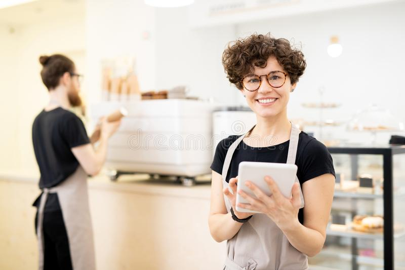 Smiling pretty waitress using tablet to take order royalty free stock photo