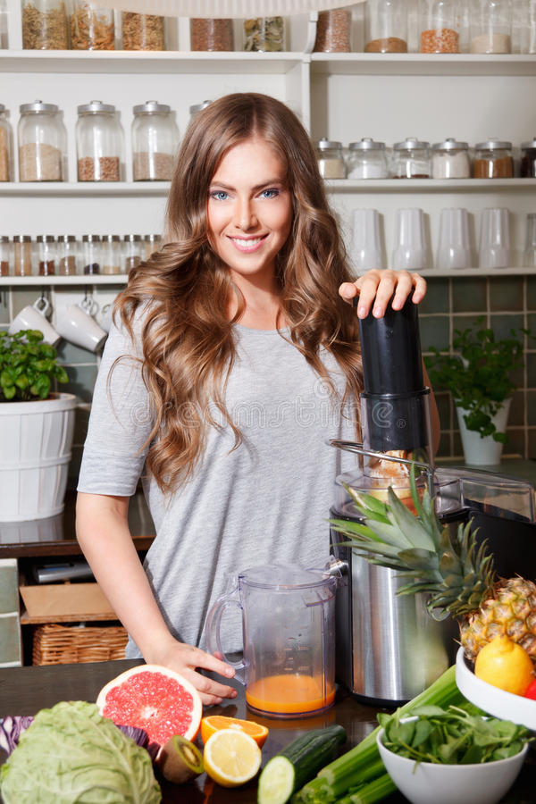 Smiling pretty woman making healthy juice royalty free stock photos