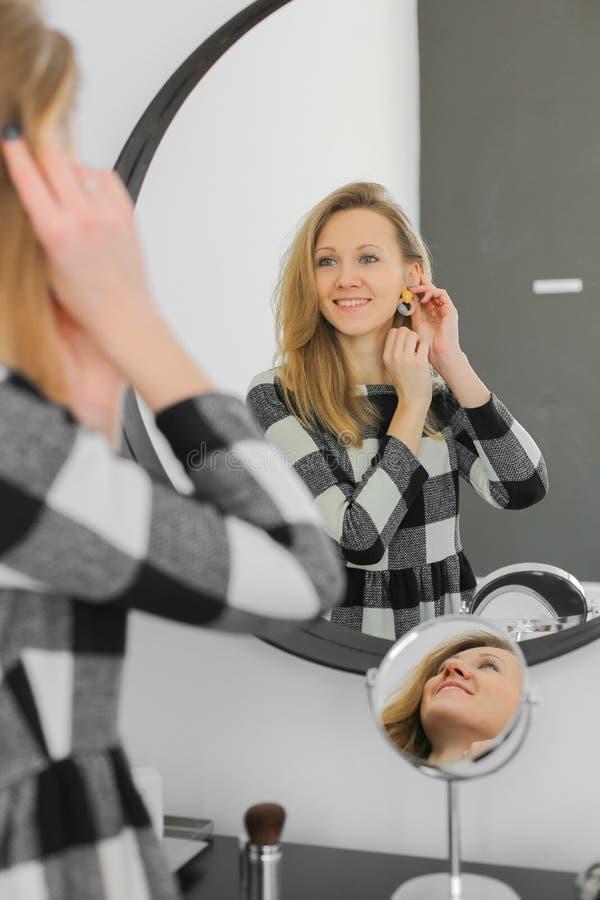 Smiling pretty woman near mirror stock photo