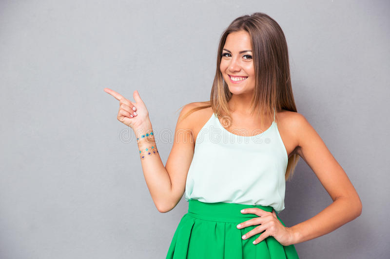 Smiling pretty woman pointing finger away stock photo