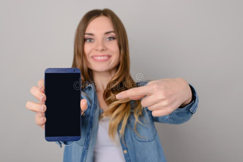 Smiling pretty woman showing black empty screen of her smartphone and pointing on it with her finger; isolated on grey background stock photography