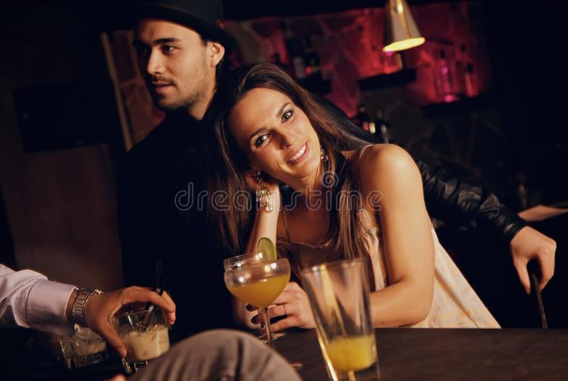 Pretty Woman Relaxing at the Bar with Friends royalty free stock images