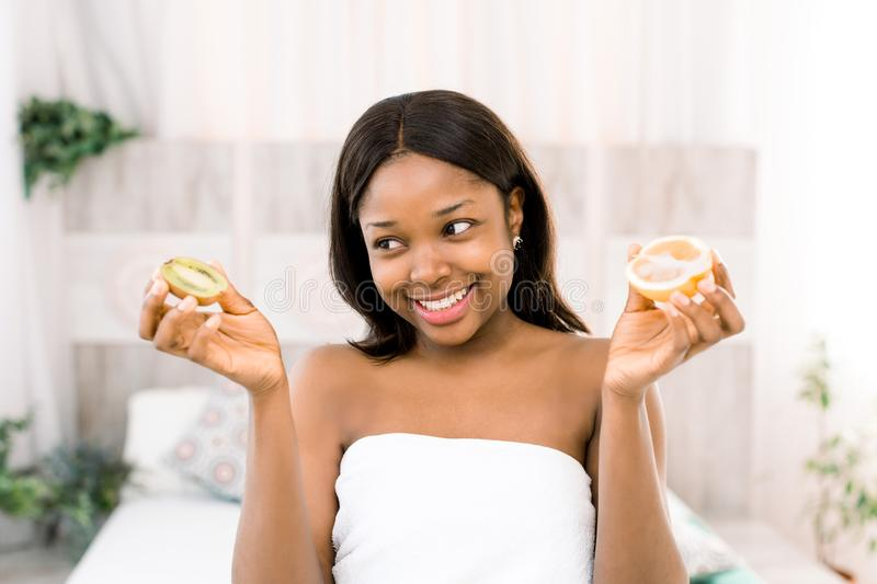 Smiling pretty young African woman holding kiwi and orange slices in hands. Isolated over light background in spa.  stock images