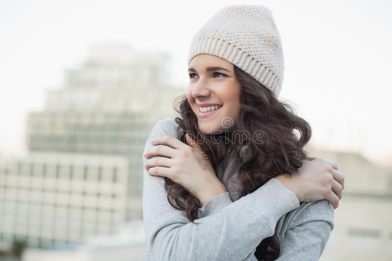 Smiling pretty young brunette shivering royalty free stock photo