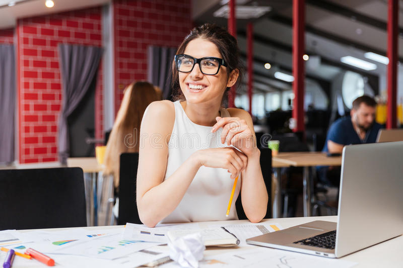 Smiling pretty young business woman in glasses sitting on workplace royalty free stock photography
