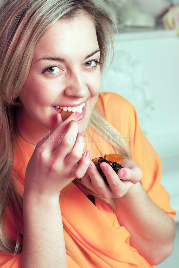 Smiling pretty young girl with dried fruits royalty free stock images