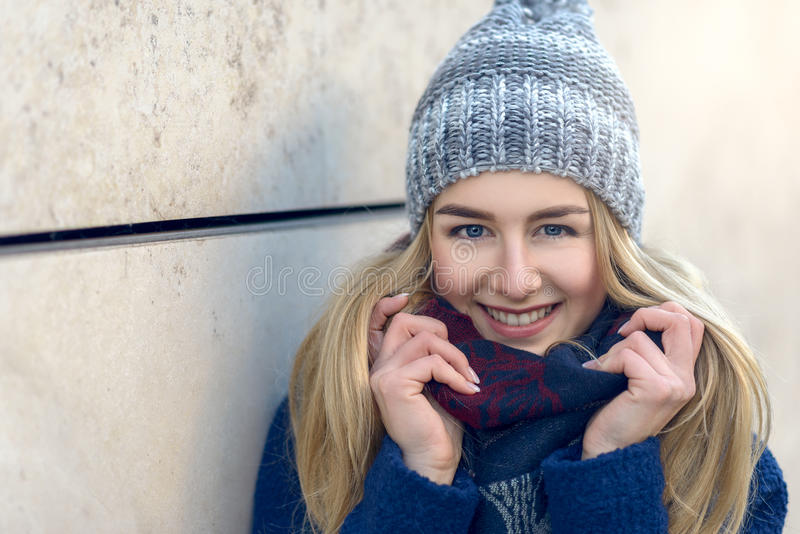 Smiling pretty young woman in a beanie. Smiling pretty young woman with long blond hair in a beanie or knitted woollen winter cap standing against an exterior royalty free stock photos
