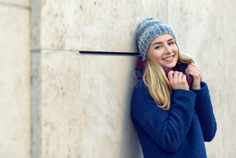 Smiling pretty young woman in a beanie royalty free stock photography