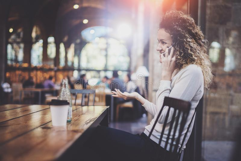 Smiling pretty young woman making conversation call with her friends via cell telephone while sending free time at city royalty free stock images