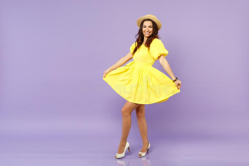 Smiling pretty young woman in yellow dress summer hat looking camera, holding skirt isolated on pastel violet wall royalty free stock photo