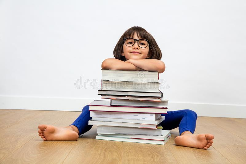 Smiling primary child with eyeglasses leaning on pile of books royalty free stock photos