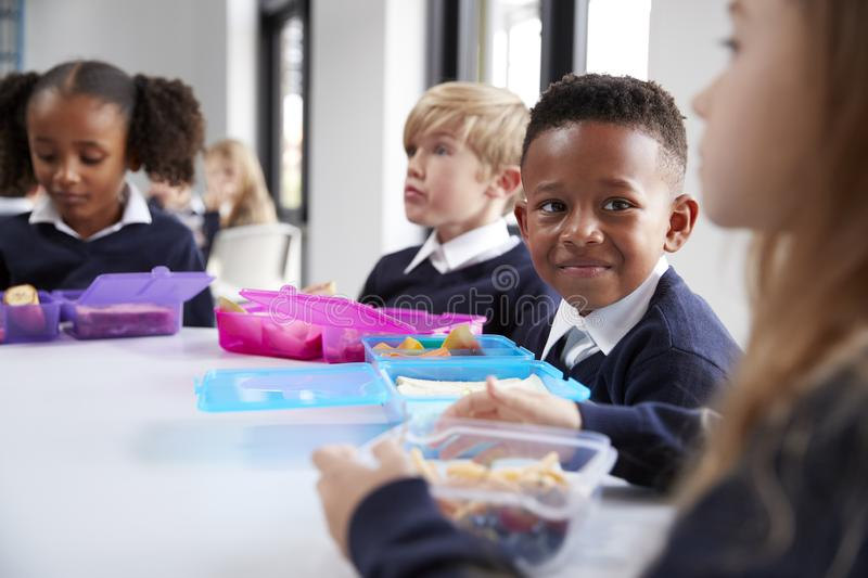 Smiling primary school kids sitting at a table eating their packed lunches together, selective focus stock image