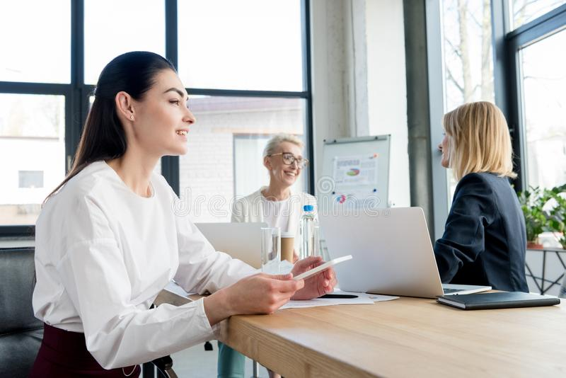 smiling professional businesswomen working with digital devices royalty free stock photo