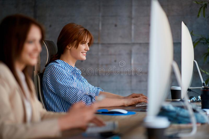 Smiling professional female designer working with computer royalty free stock image