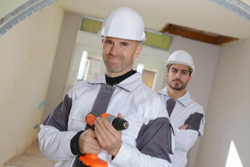 Smiling professionals team builders watching indoor site around. Smiling professionals team of builders watching the indoor site around royalty free stock image