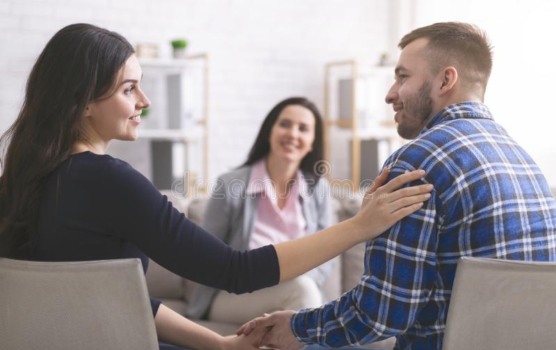 Smiling psychologist looking at happy couple after effective marital therapy. Peace in family. Smiling psychologist looking at happy couple after effective and stock image
