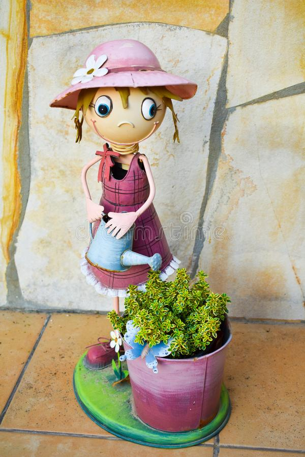 Smiling puppet made in colorful steel that shows a happy cross-eyed girl watering can a bucket with a green plant on a yellow royalty free stock photo