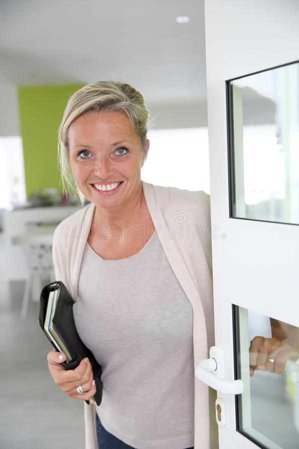 Smiling real-estate agent woman. Real-estate agent presenting modern house royalty free stock photos