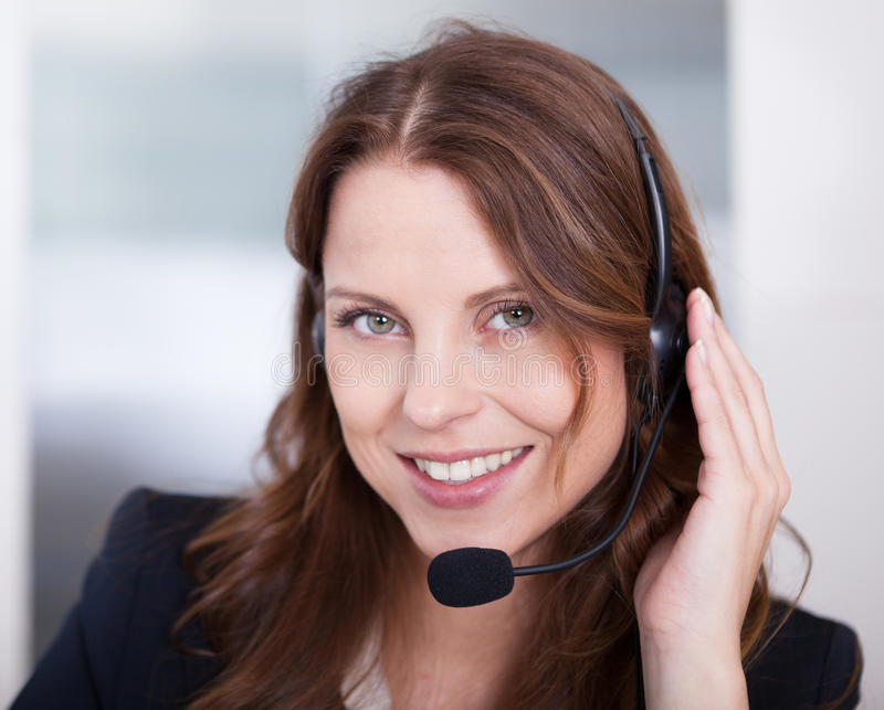 Smiling receptionist or call centre worker. Sitting typing at a computer while speaking into a headset with a microphone stock photo