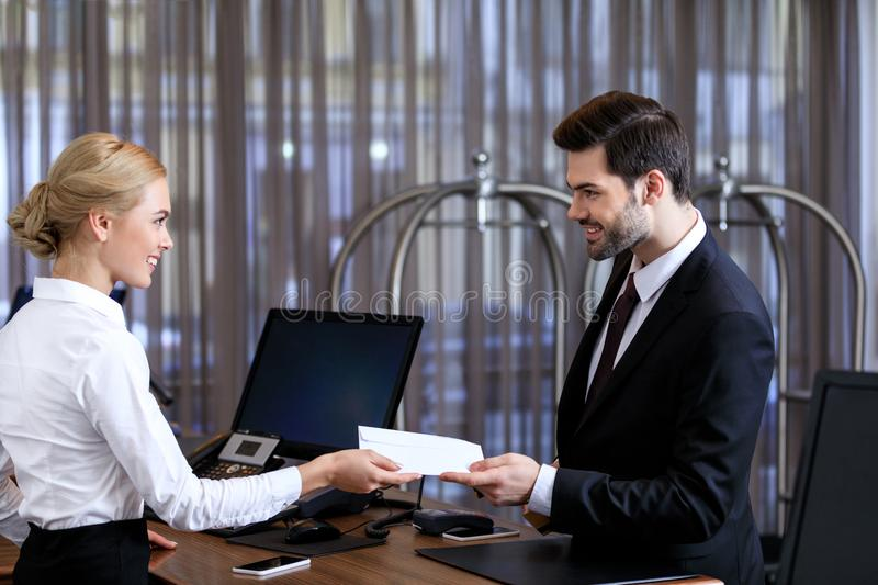 Smiling receptionist giving envelope to businessman. In hotel royalty free stock image