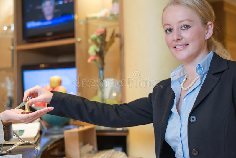 Smiling receptionist handing over room keys. Smiling attractive young female receptionist in a hotel lobby handing over room keys to a woman client in a stock photo