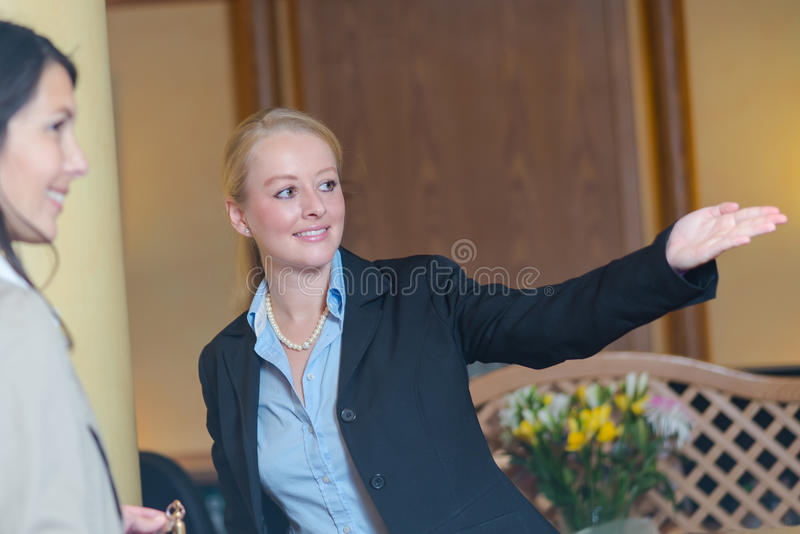 Smiling receptionist helping a hotel guest. Beautiful friendly smiling receptionist behind the service desk in a hotel lobby helping an attractive female guest royalty free stock image
