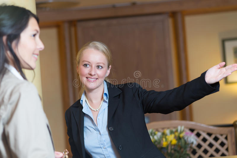 Smiling receptionist helping a hotel guest. Beautiful friendly smiling receptionist behind the service desk in a hotel lobby helping an attractive female guest royalty free stock photo