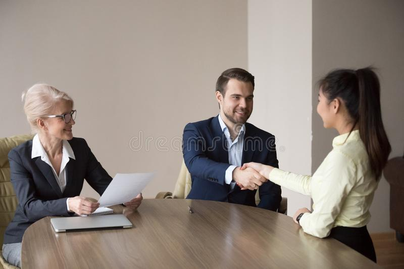 Smiling recruiter handshaking successful job applicant at interv. Smiling recruiter shaking hand of female employee greeting her at interview, HR manager royalty free stock photos