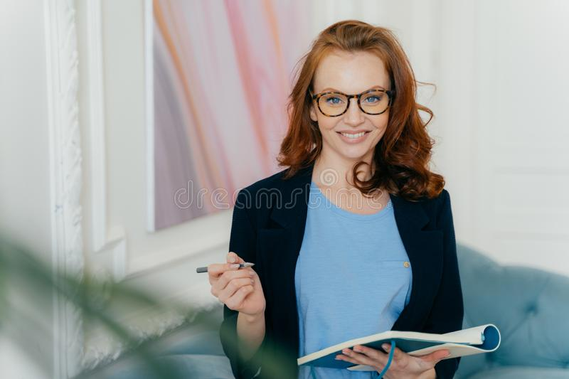 Smiling red haired female writes notes in notepad, holds diary and pen, wears formal suit,, spectacles, poses indoor, listens stock photos