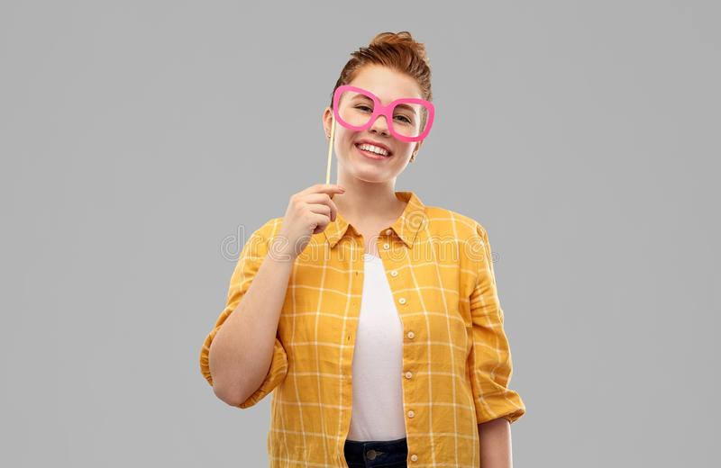 Smiling red haired teenage girl with big glasses royalty free stock photography