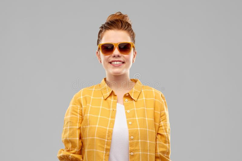 Smiling red haired teenage girl in sunglasses stock photos