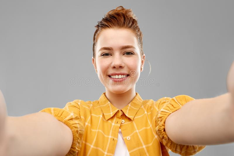 Smiling red haired teenage girl taking selfie royalty free stock photo